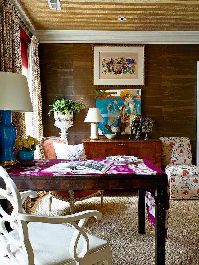 White wooden chair, orange accent chair, dark brown wooden desk, and hazel dresser in living room