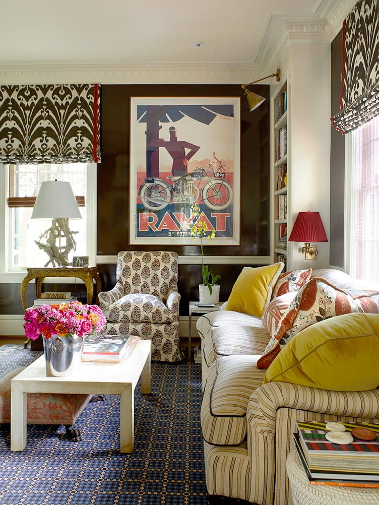 Striped sofa, light brown wooden coffee table, leaf patterned armchair, and vintage poster in living room