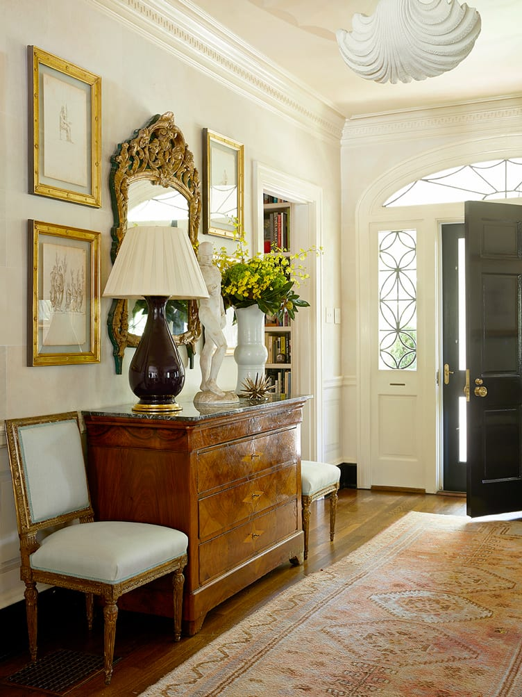 twin accent chairs, vintage dresser, standard wine lamp, and geometric runner in entryway