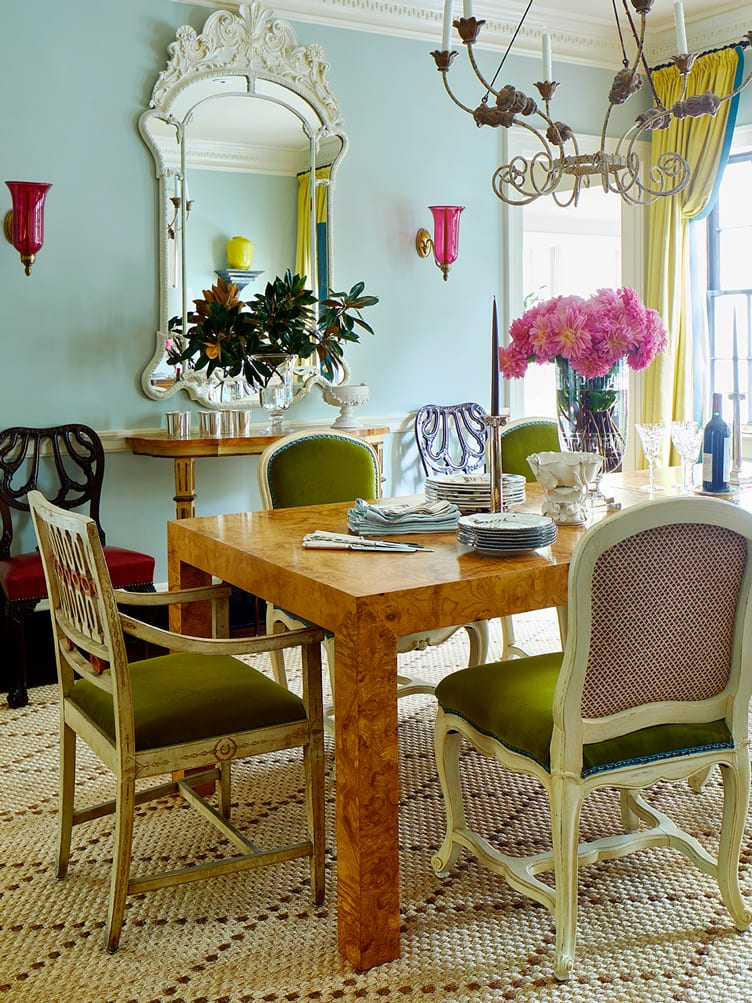 Finished wood table, and vintage green chairs under candelabra