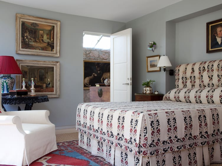 Queen sized bed, white chair, and impressionist paintings in bedroom