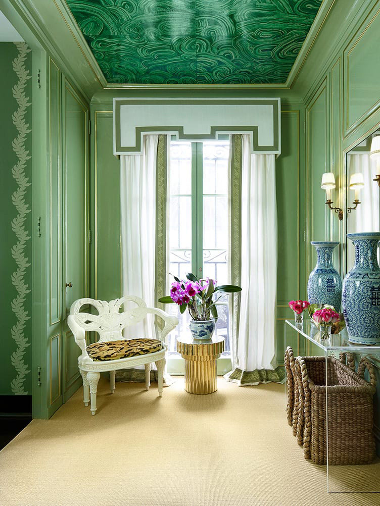 Green paneled room, malachite wallpaper ceiling, white plaster chair, blue and white urns, seagrass basket