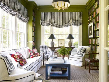 Green painted room, striped window treatments, white sofas, suzani pillow