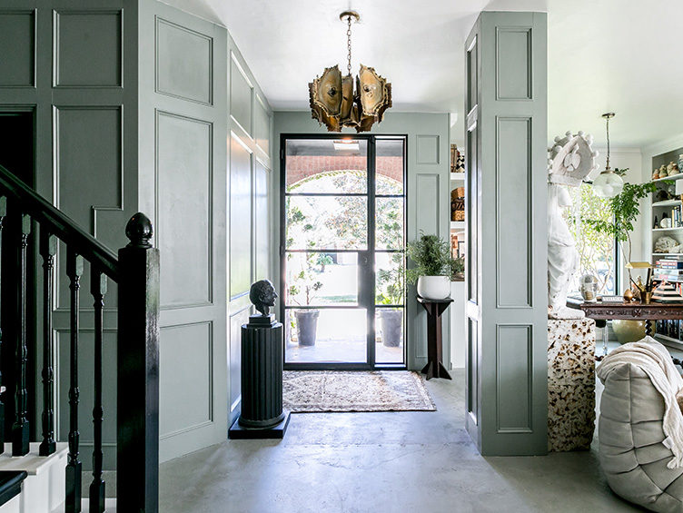 Green paneled entryway, Brutalist chandelier, pedestal with bust, cement floors, eclectic decor
