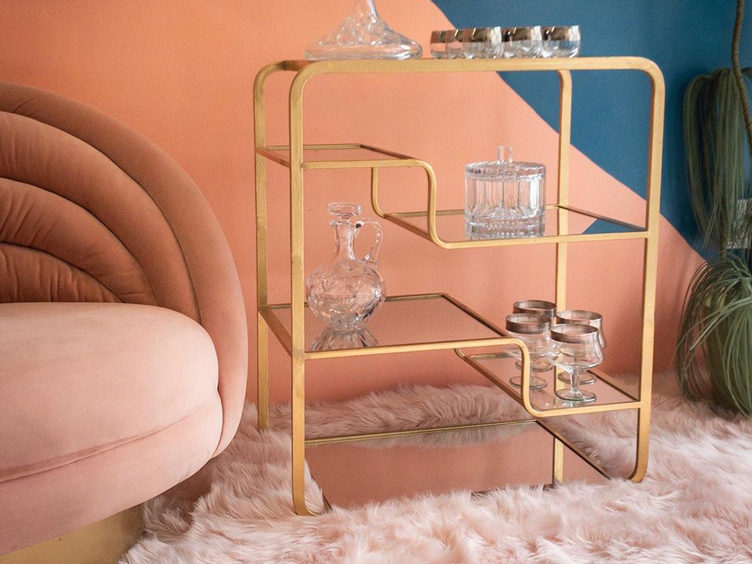 best vintage stores LA pink velvet accent chair brass shelving glassware