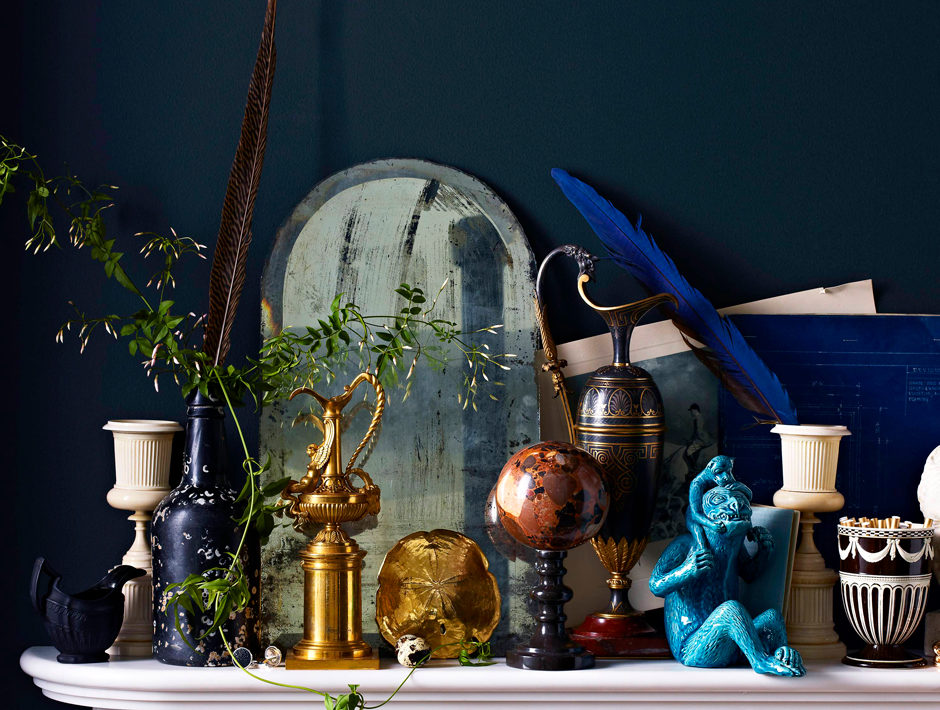 Vintage knick knacks arranged on marble fireplace mantle backed by a deep navy blue wall