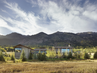 The house, designedbyarchitect Blaze Makoid,is madeofquarried stone,reclaimed barnwood, and vast expanses of glass, andwas sited to make the most of the stunning mountain views.