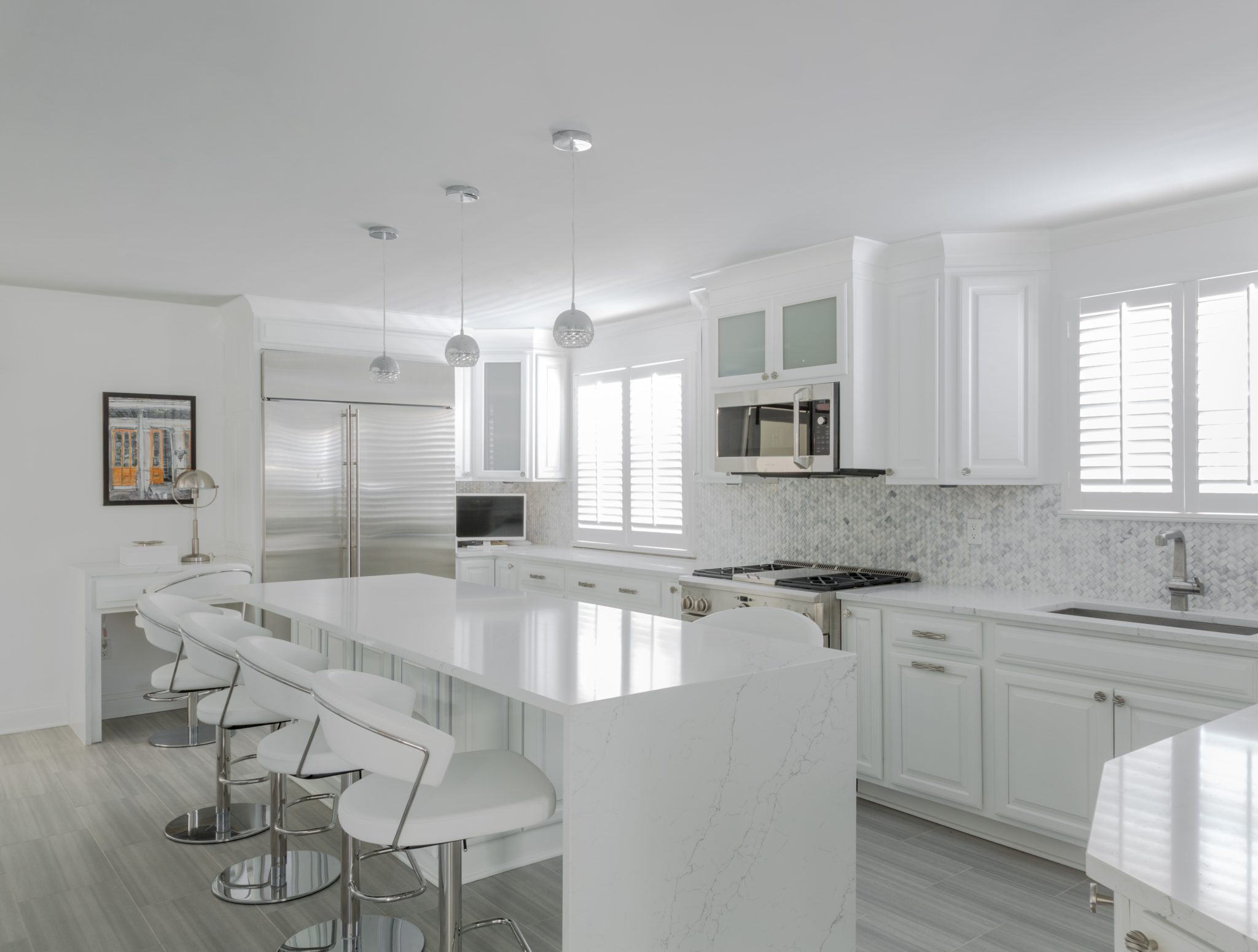 Modern all white kitchen with waterfall quartz slab on centralized island by Eclectic Home