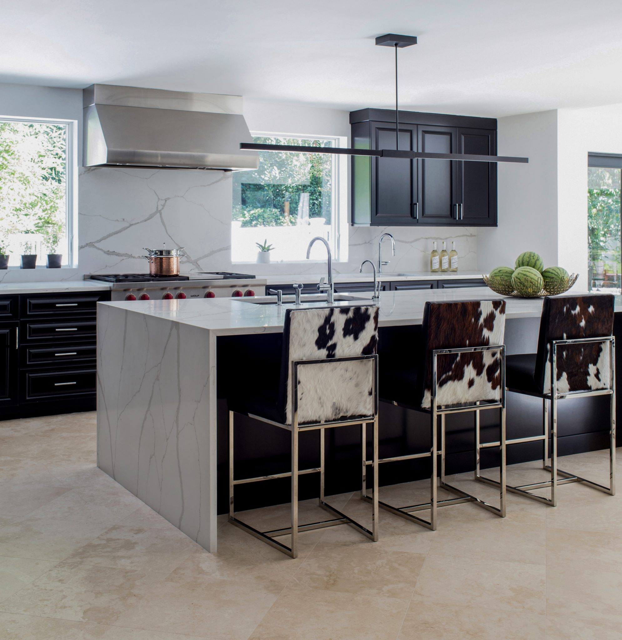 Custom counter stools in contemporary black kitchen with waterfall island by Abaca Interiors