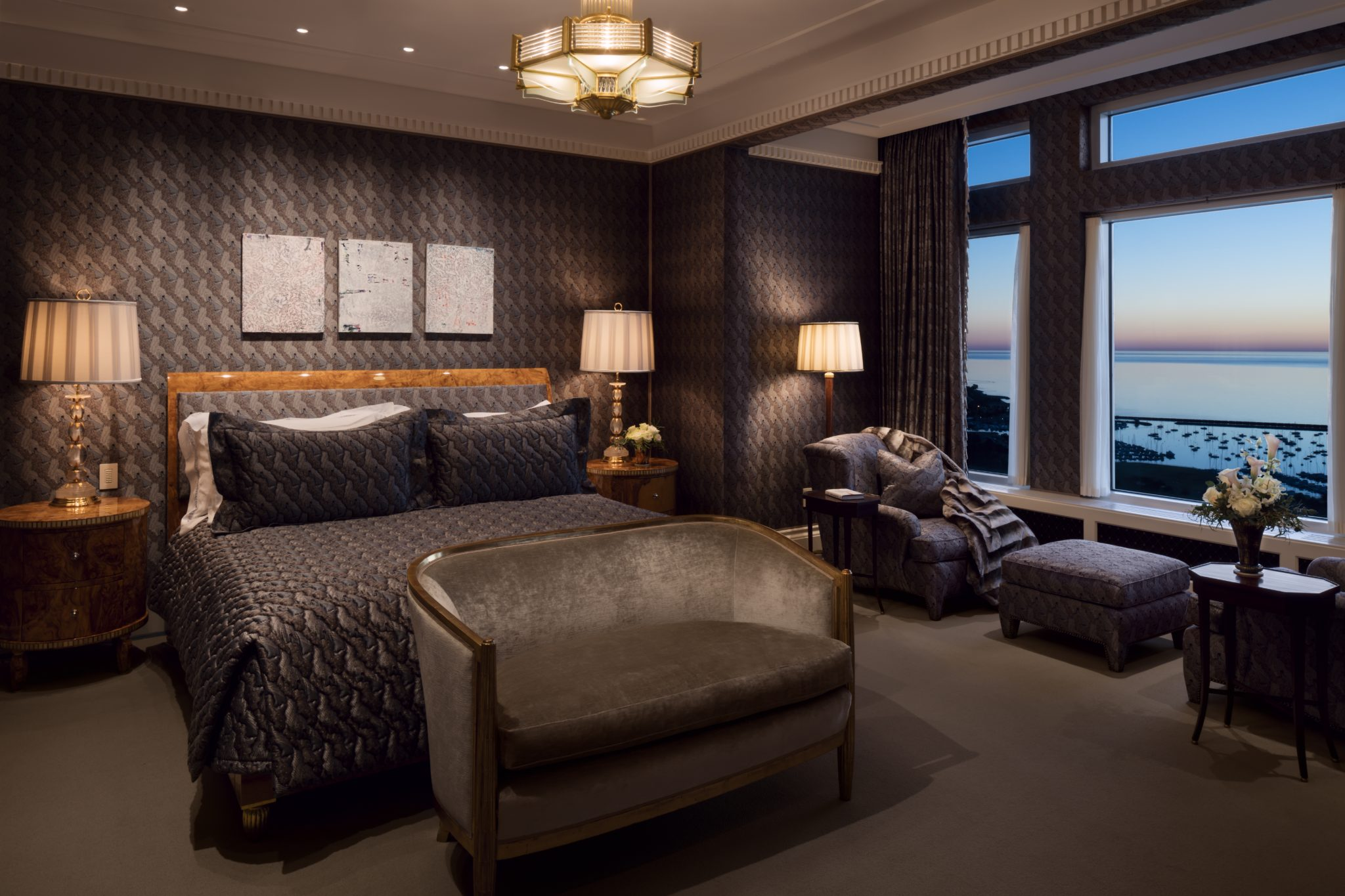 The master bedroom with water views is decorated in smoky textures and tones. By Wade Weissmann Architecture Inc.