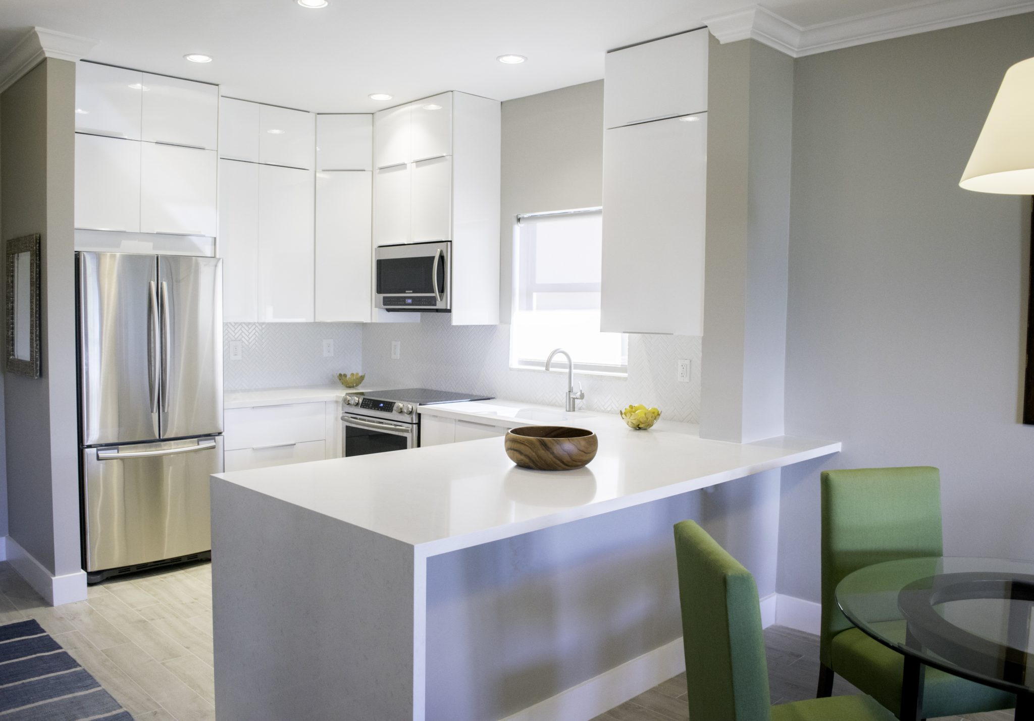 Modern Key Biscayne Kitchen in high-gloss white cabinetry and waterfall surfaces by mr. alex TATE