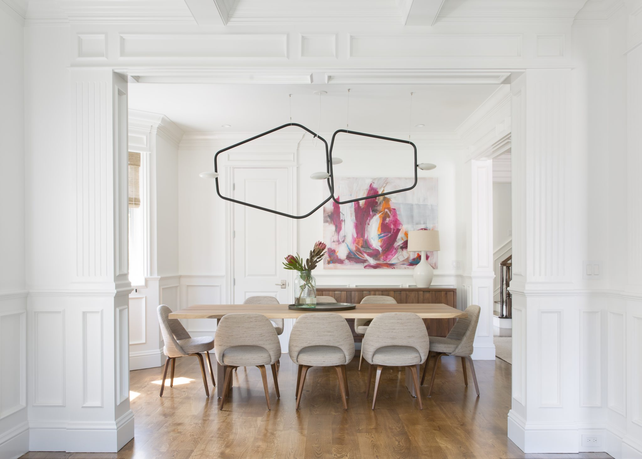 Bright dining room with modern chandelier, midcentury chairs, custom wainscot. by IDF Studio