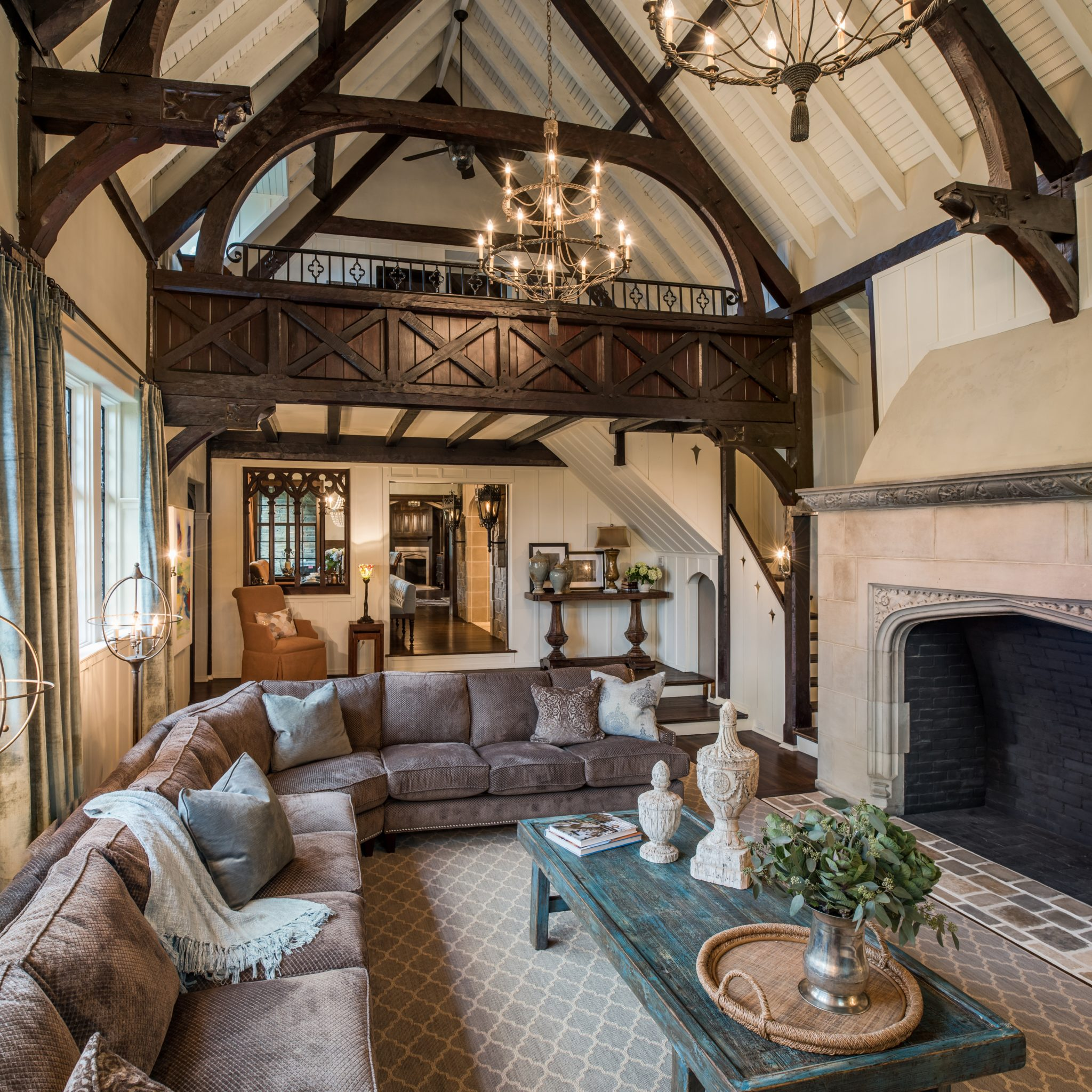 Tudor style family room with large stone fireplace and loft by Period Architecture