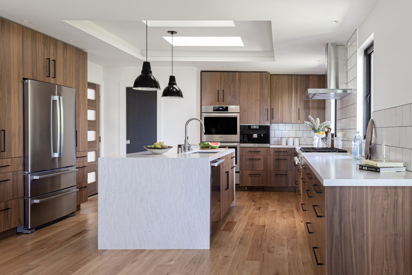 Contemporary Kitchen with Walnut Cabinetry and Waterfall Island by Florence Livingston Interiors