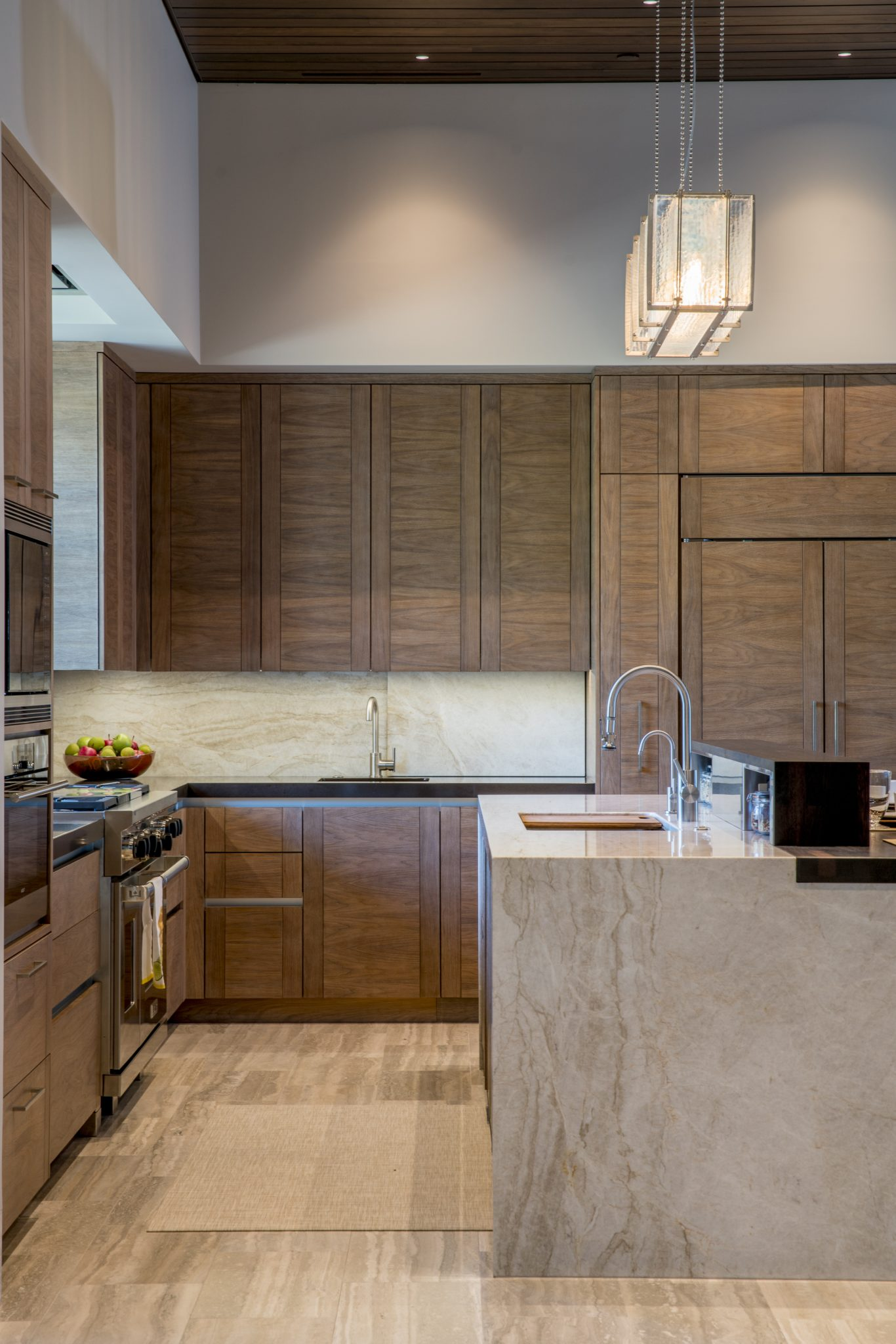 Desert kitchen with warm walnut cabinets and waterfall island. by Cooper Pacific Kitchens