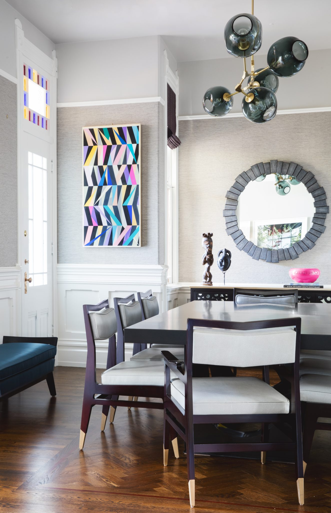 Dining room with stained glass panel, contemporary art, and herringbone floor by Jeff Schlarb Design Studio