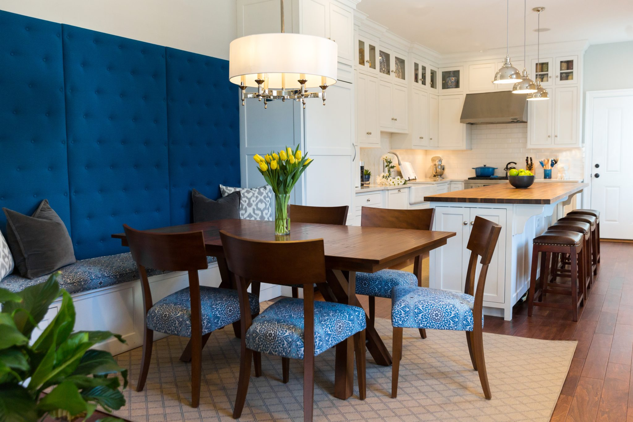 An open concept white kitchen and dining room with a custom banquette. By Laura Hodges Studio