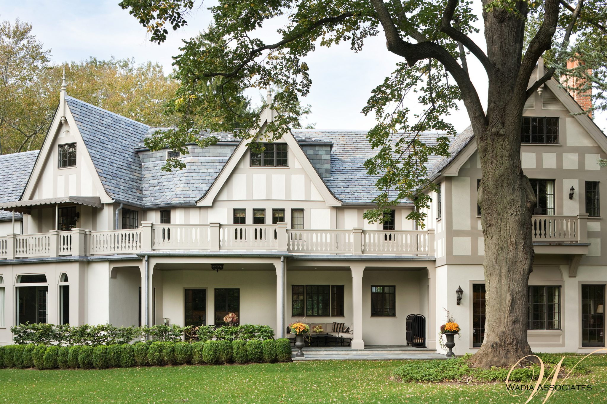 A grand view of this American Tudor Arts & Crafts home's welcoming exterior across the front lawn. by Wadia Associates