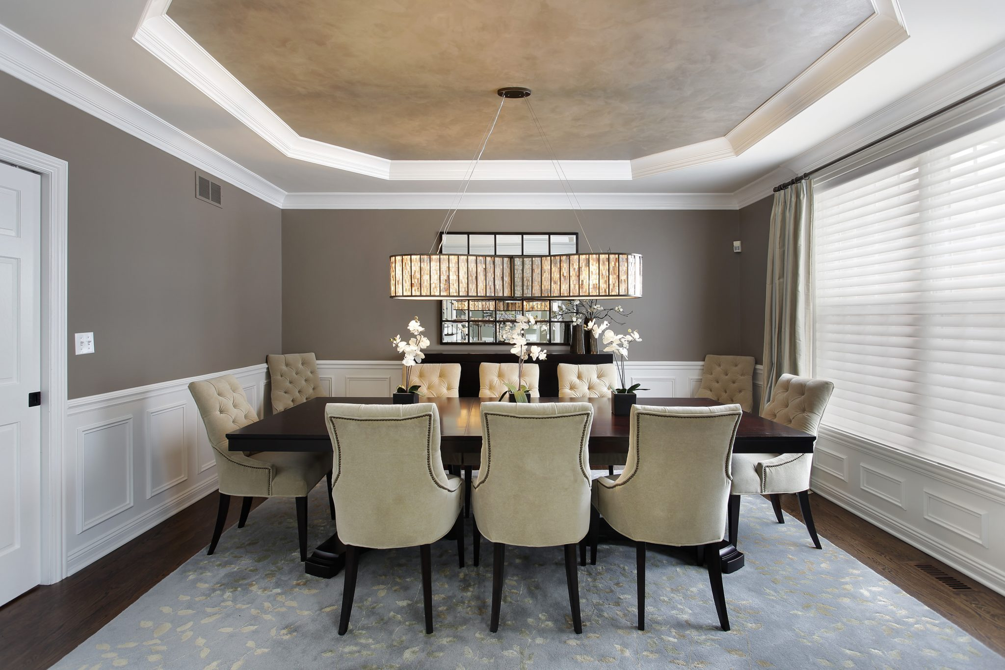 Dining table with chandelier, faux finish ceiling, tufted chairs, wainscoting by Interior Enhancement Group