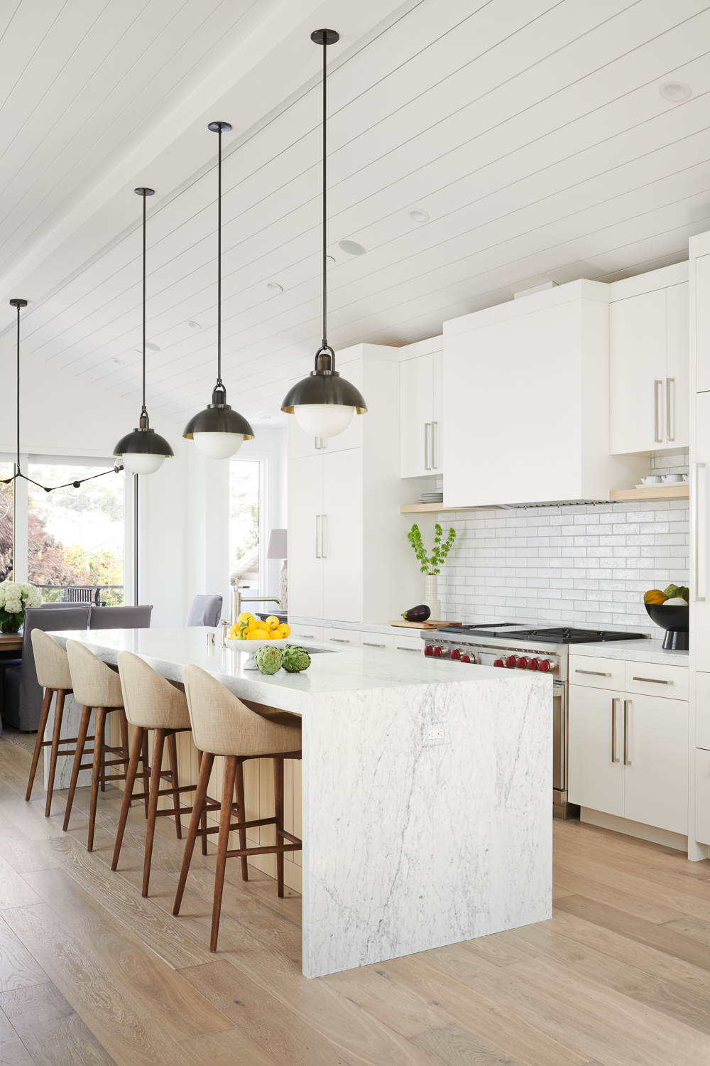 Bright kitchen with marble waterfall island, pendants, and barstools by Holly A. Kopman Interior Design