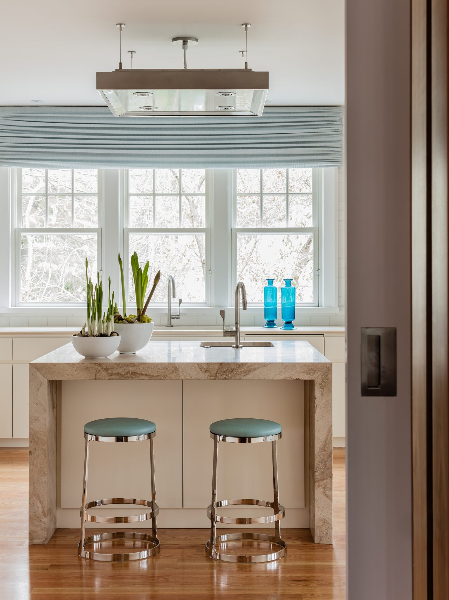 Wellesley Family Home, Kitchen island with marble countertops that waterfall by Platemark Design