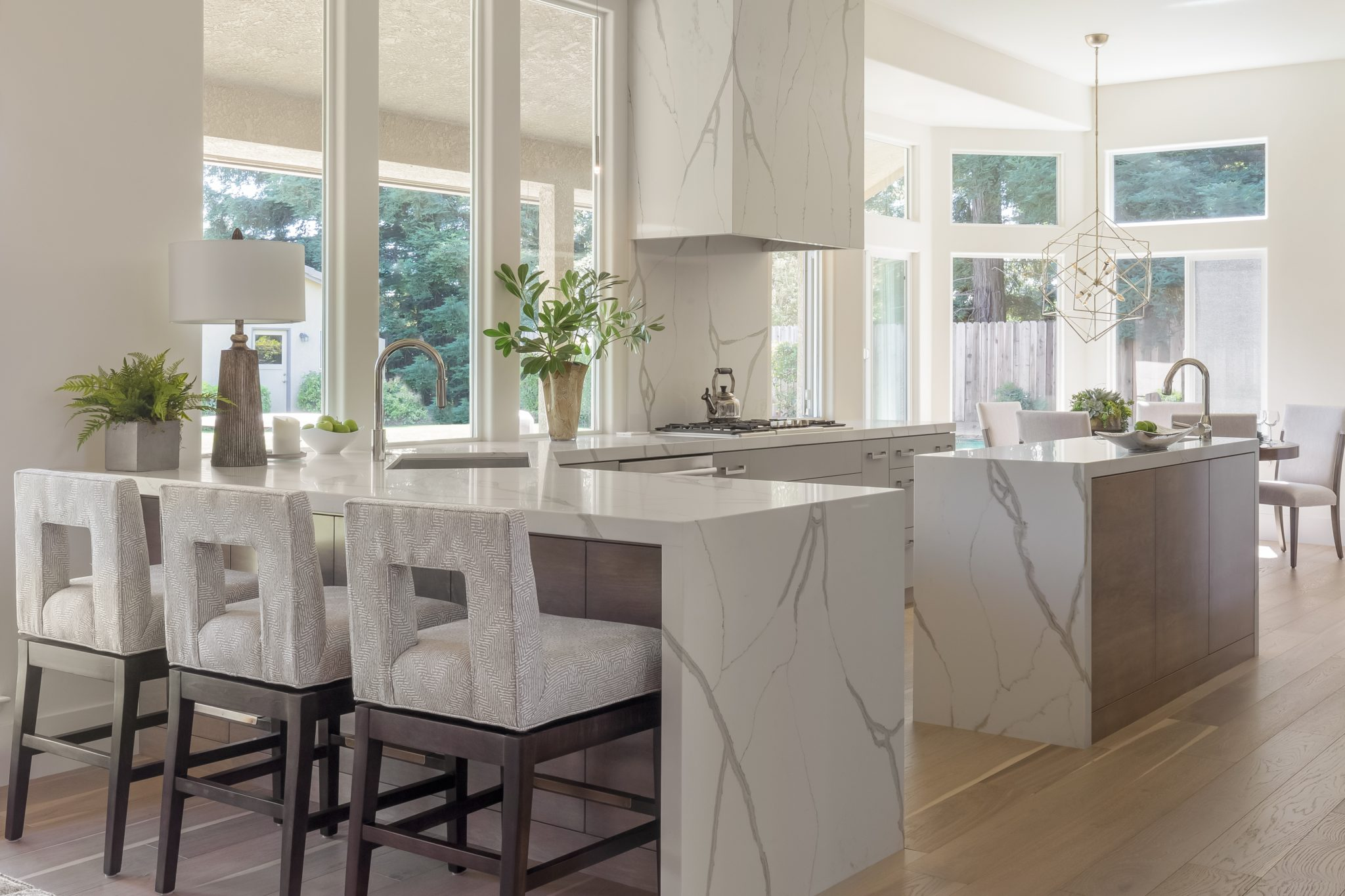 Contemporary Kitchen with windows surrounding, quartz hood, waterfall counters by Wendy Glaister Interiors