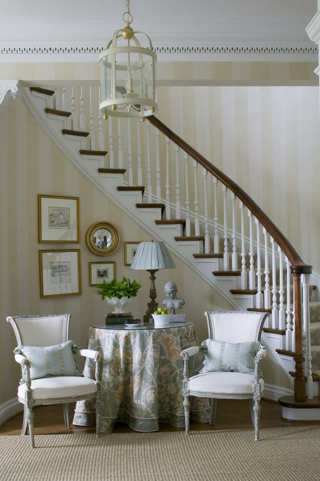 A sitting area completes this formal foyer by Kelley Interior Design