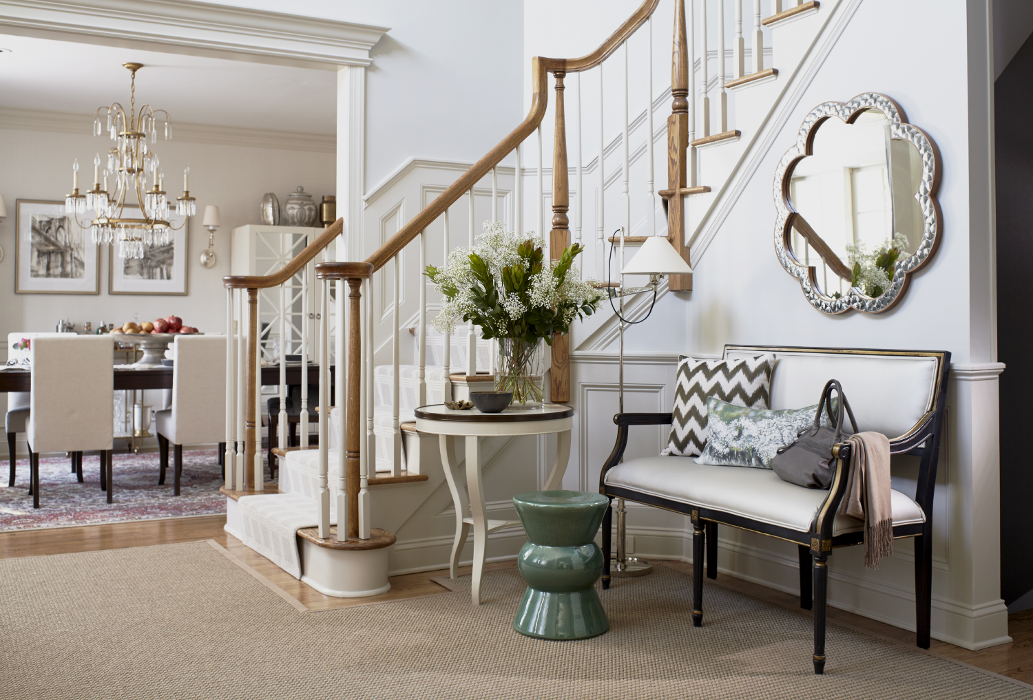 Foyer with French bench in white leather, sisal carpet, and accent table. By Uma Stewart Interiors & Lifestyle
