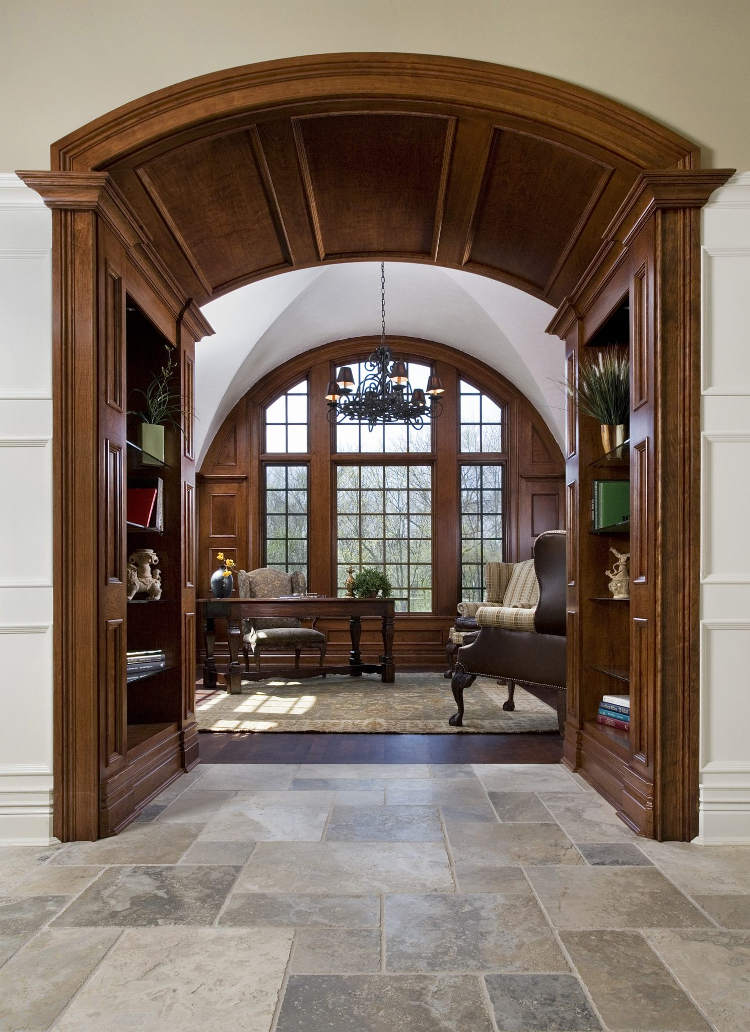 Arched entry with flanking bookshelves lead to paneled library by Orren Pickell Building Group