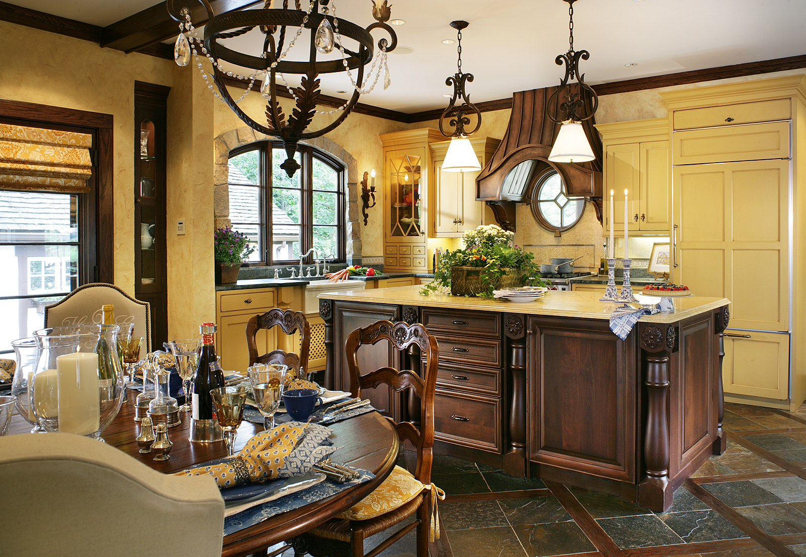 French country kitchen with timeless Old World ambiance, featuring mustard-colored cabinets, wrought iron light fixtures, limestone and soapstone counters, and slate and wood floor. By J. Stephens Interiors