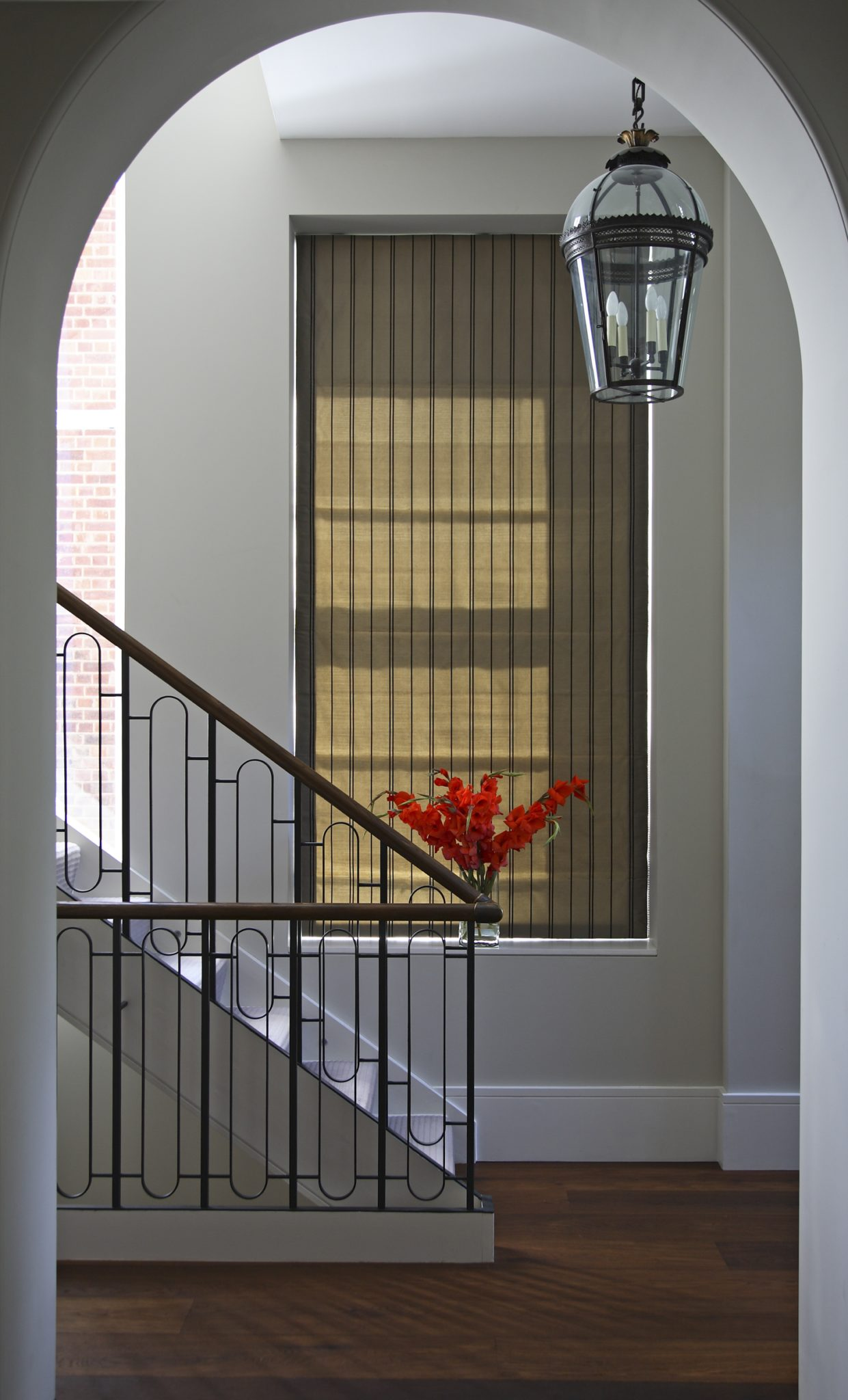 Entrance Hall with striking bespoke staircase and Jamb lighting by dk INTERIORS