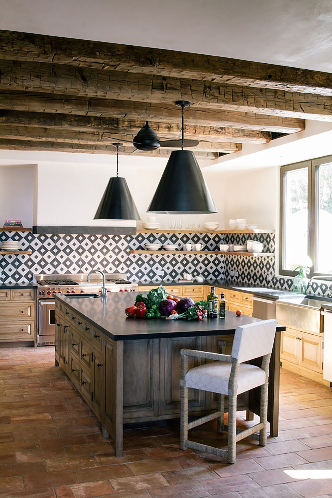 Kitchen featuring black and white tile and vintage beams by Chris Barrett Design