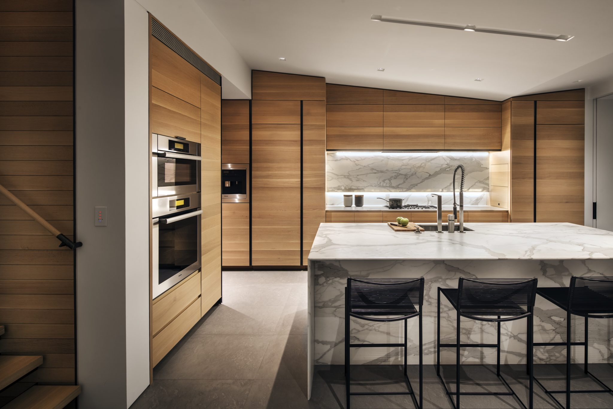 Modern kitchen with Calcutta Gold marble island and backsplash by Monica Fried Design