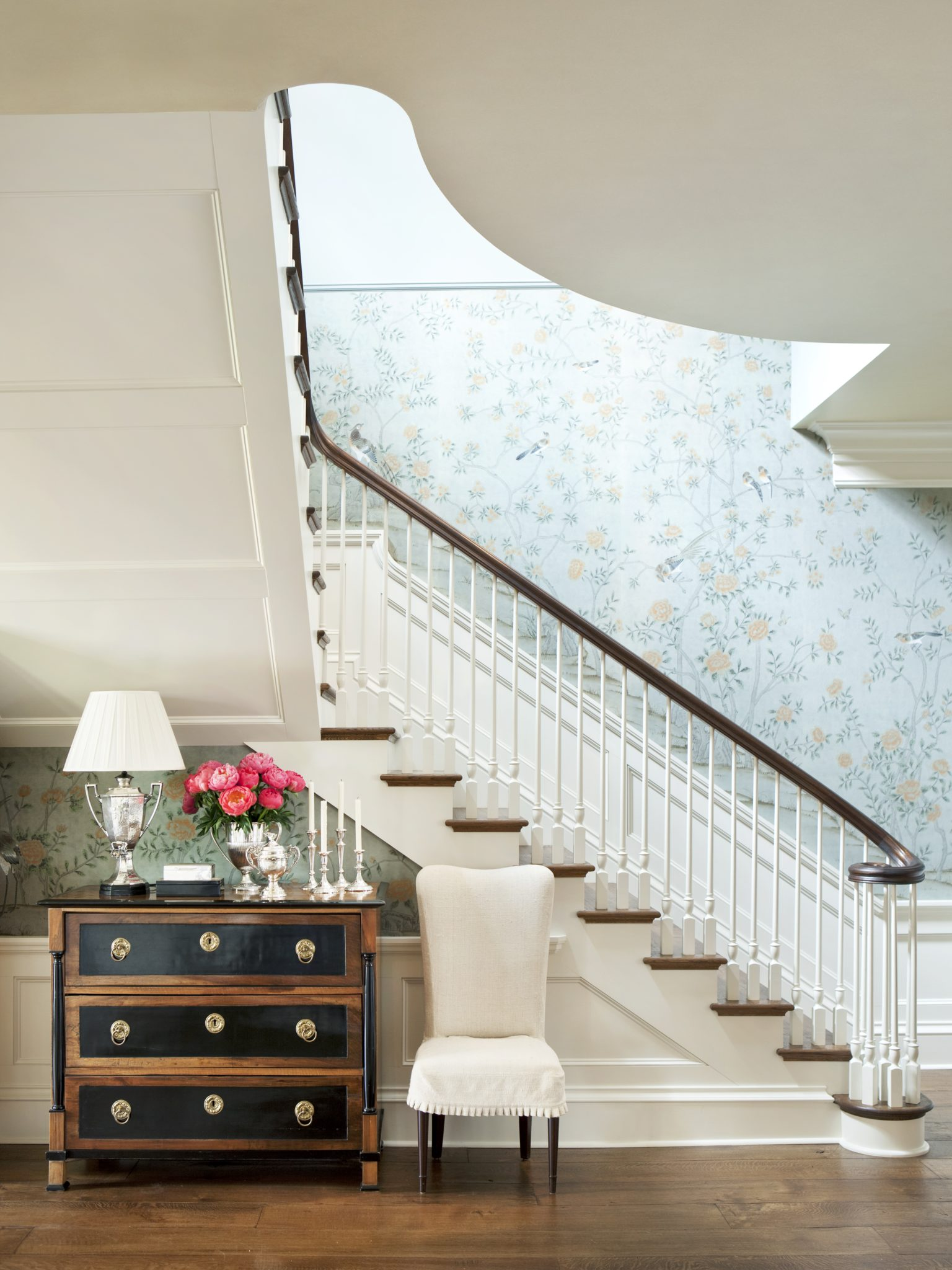 Relaxed foyer and staircase with blue floral wallpaper by Suzanne Kasler Interiors