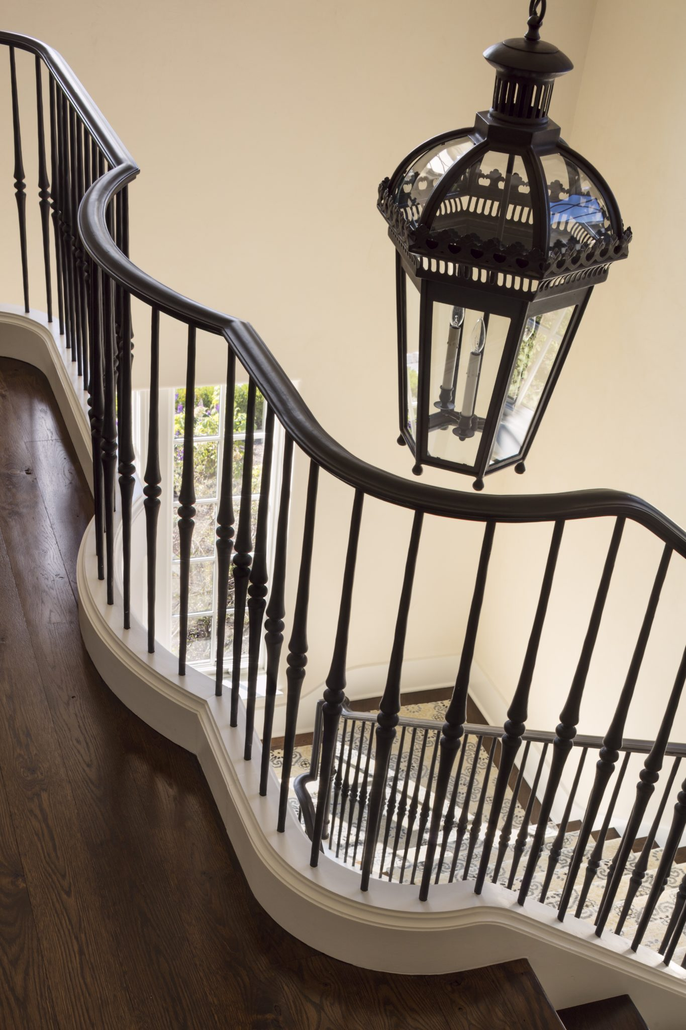 The finely detailed hardwood bannister is juxtaposed by a white painted base. by Wade Weissmann Architecture Inc.