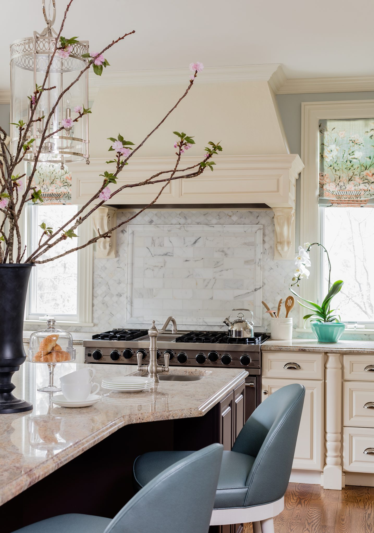 Transitional kitchen with Carrara backsplash and blue leather counter stools by Robin Gannon Interiors