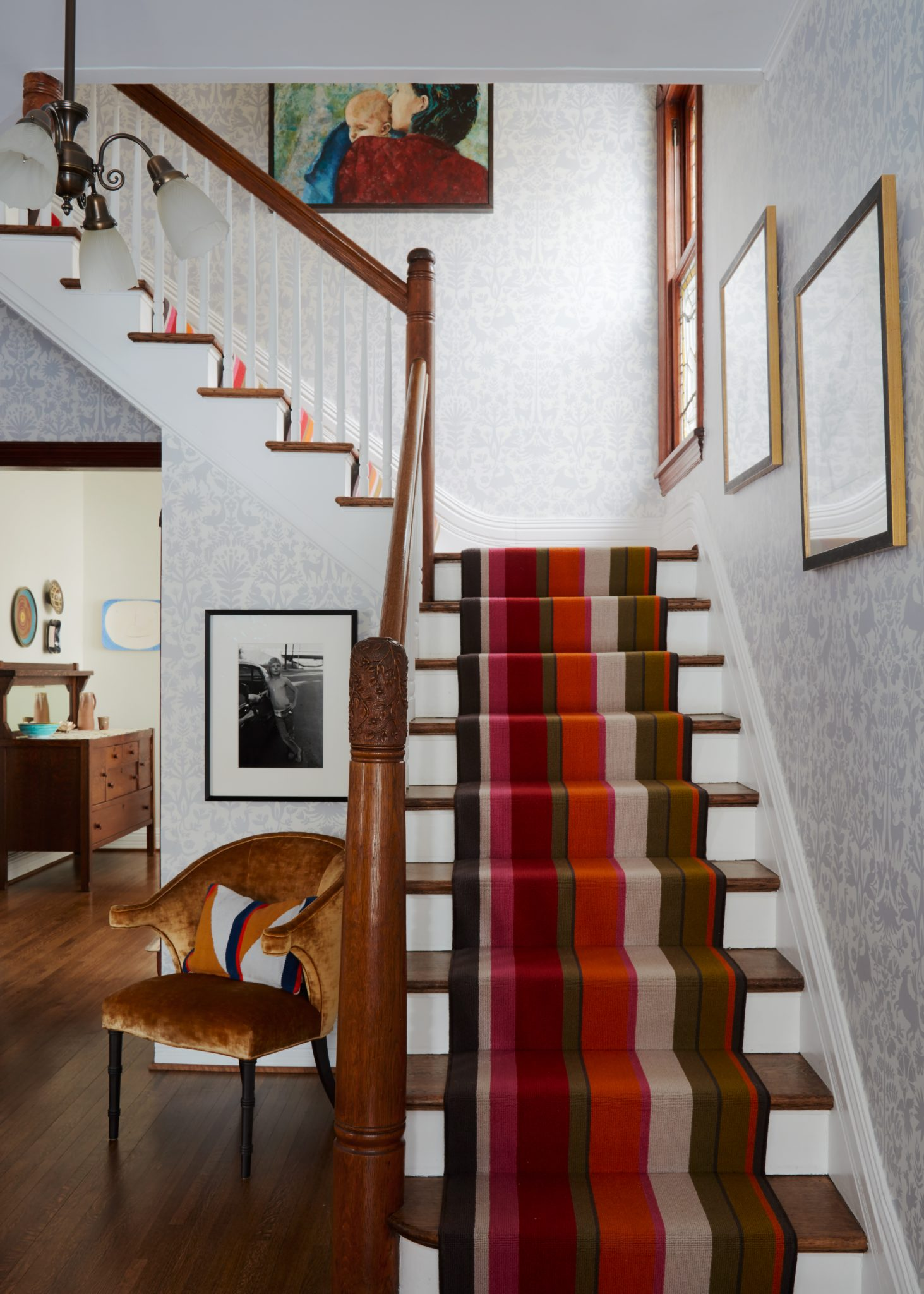 Entry stairs with colorful runner and wallpaper by 2to5 Design