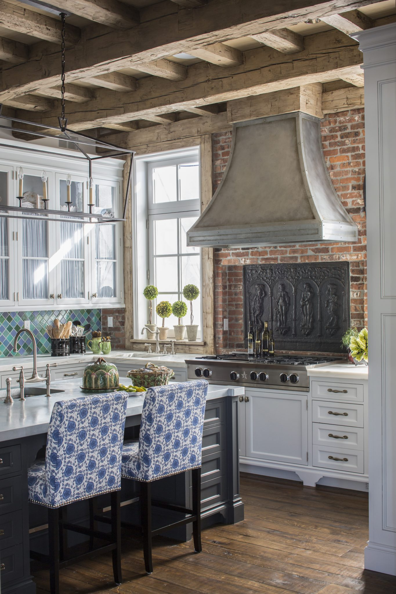 A cast iron decorative piece adorns the brick backsplash behind the silver hood. By Sarah Blank Design Studio
