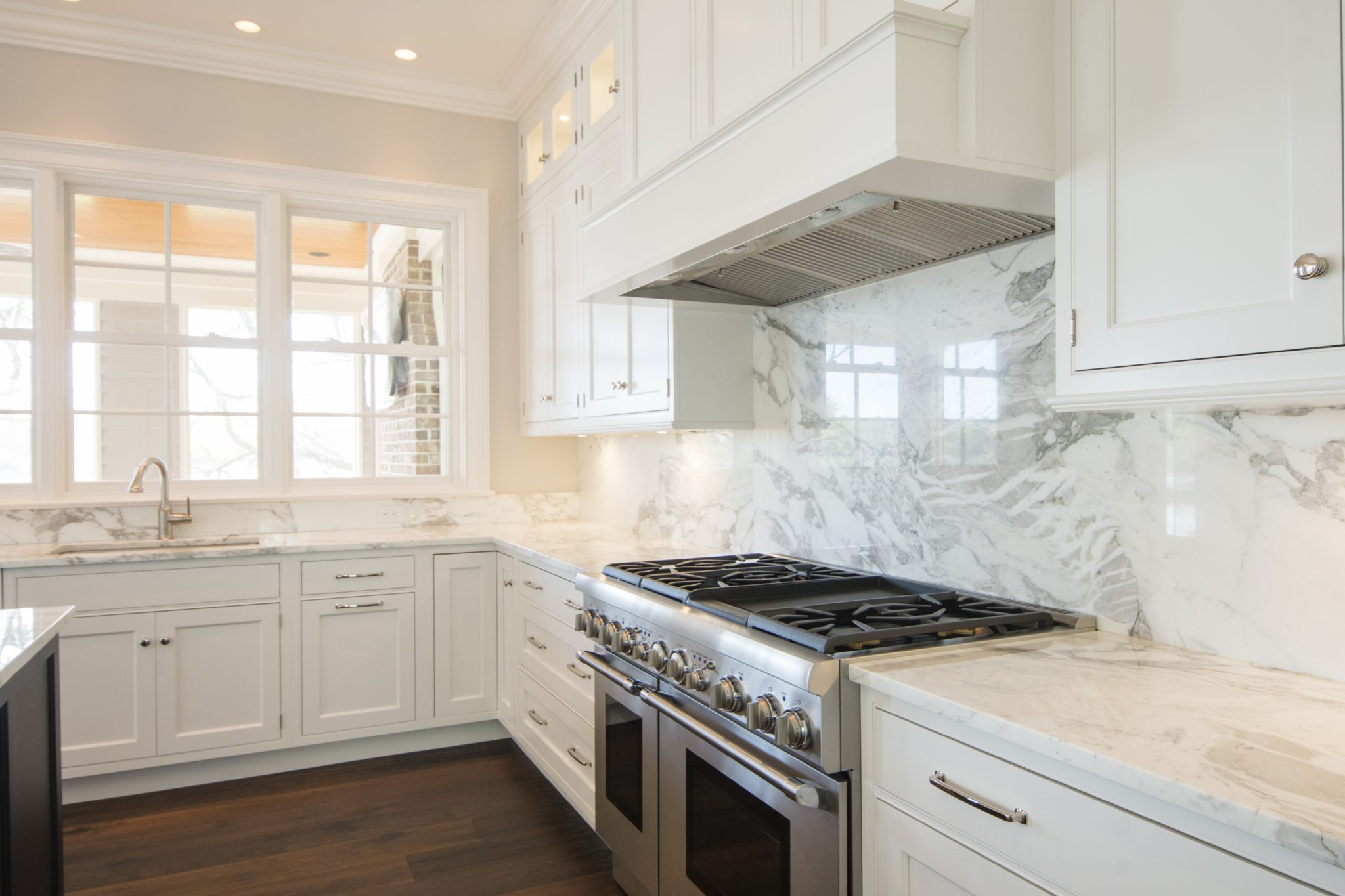 Kitchen with white cabinets and full height marble slab backsplash by Island Architects
