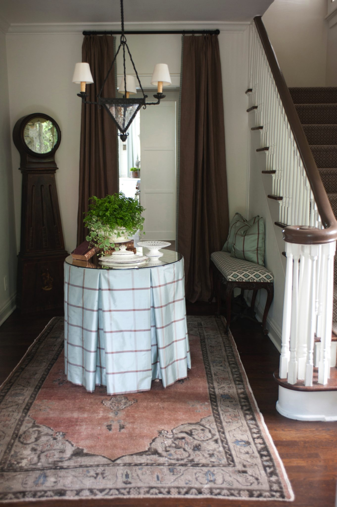 Charming entryway with skirted table and oushak rug by Lauren DeLoach Interiors