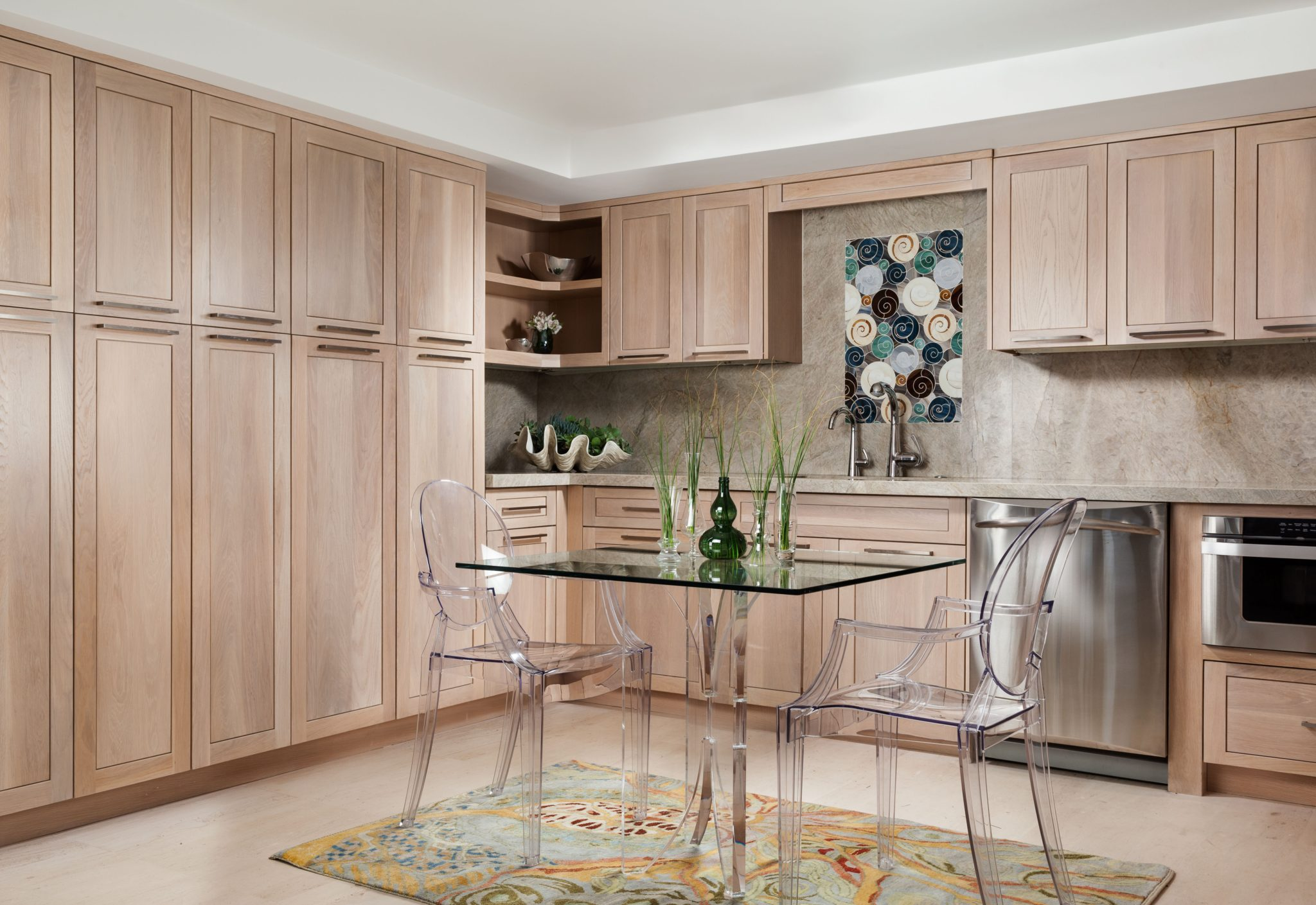 The kitchen features light wood tone cabinetry complementing a natural stone floor, a marble backsplash and light marble countertops. By Gil Walsh Interiors