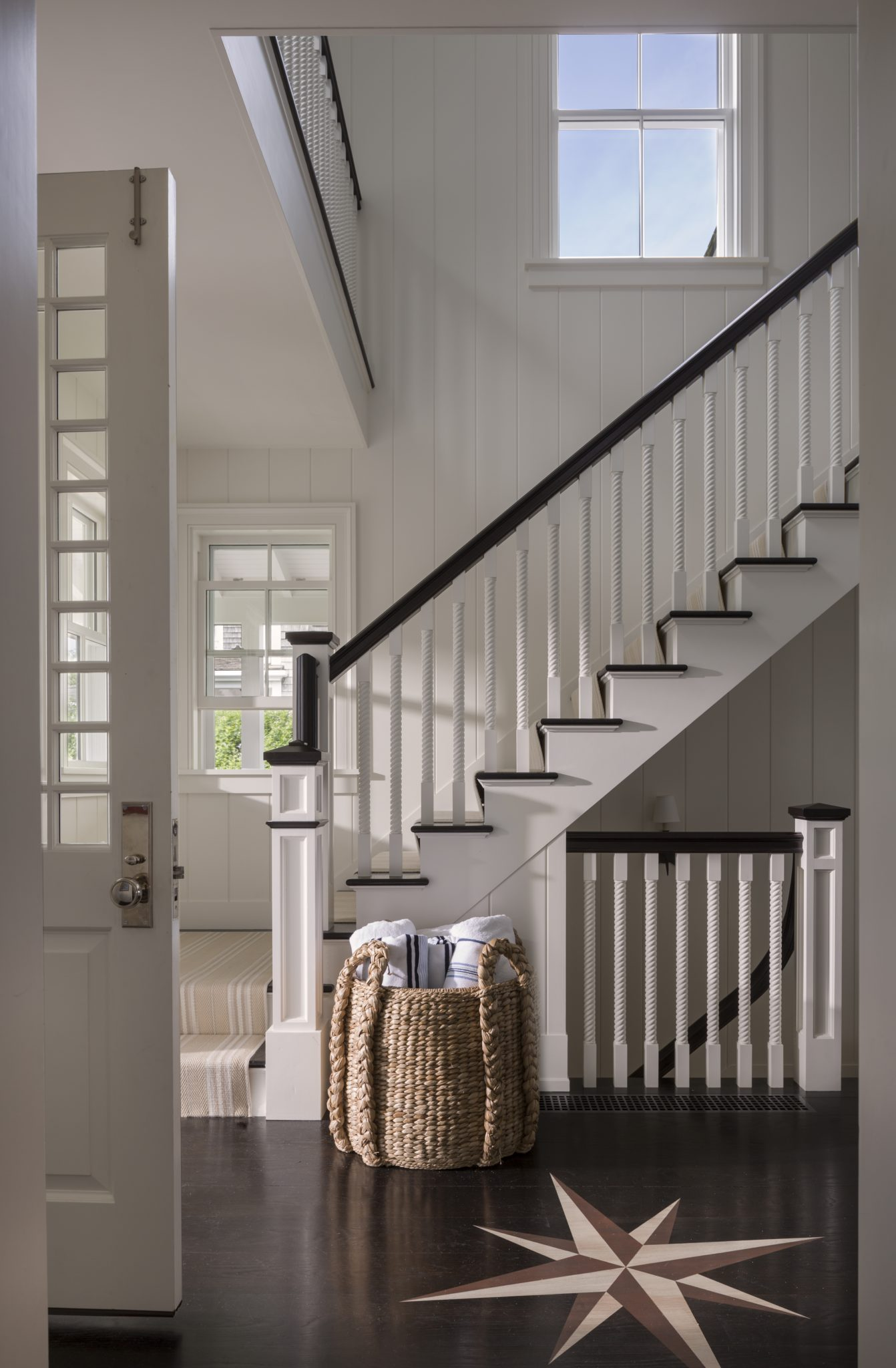 Airy entry way with starburst floor inlay, white molding and dark wood accents by SLC Interiors