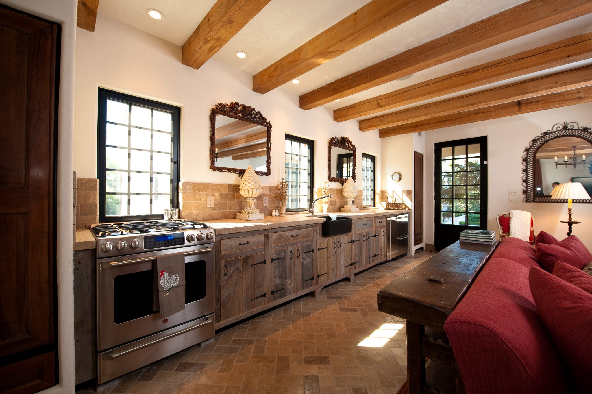 Kitchen with Reclaimed Beams, Barn Board Cabinets and Herringbone Stone Floor by Island Architects