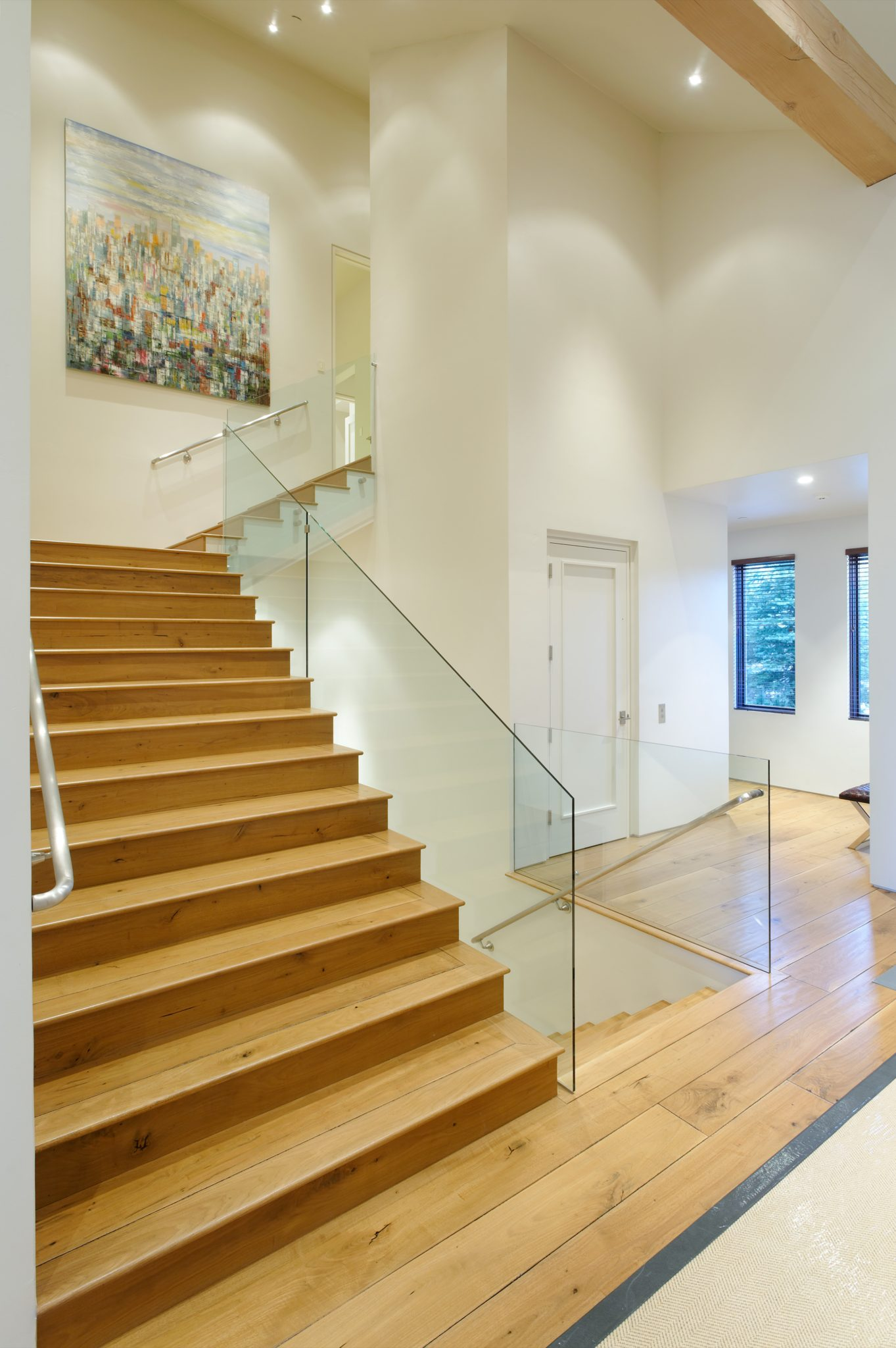 Blonde wood stairway with glass railing. by Brewster McLeod Architects