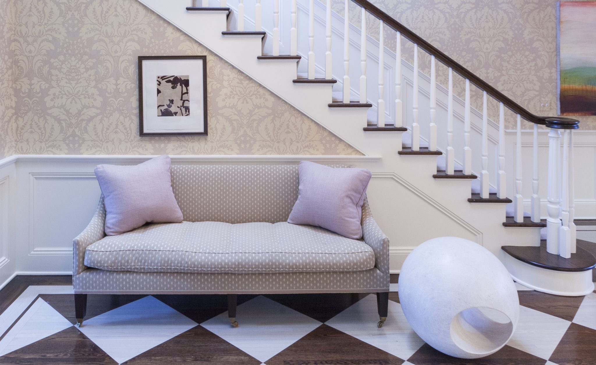 Foyer with a custom made settee and stained wood floor with stencil pattern by Liliane Hart Interiors