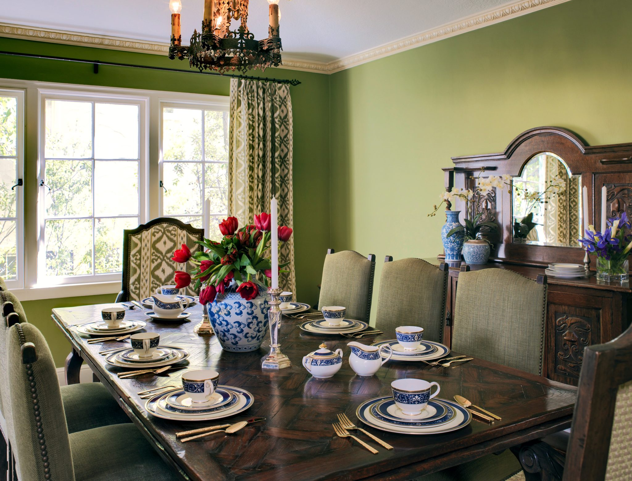 "Benjamin Moore's Mountain Lane (#488)  ""Our goal was to give this dining room vibrancy and new life while incorporating the client's antique furniture. The juxtaposition of the rich wood furniture against the dynamic backdrop of this saturated green enlivened and enriched the space and highlighted the graphic Ikat print used for the drapery and on the captain's chairs.""  Jana Meewes Magginetti, of Julianne Quelle Design"