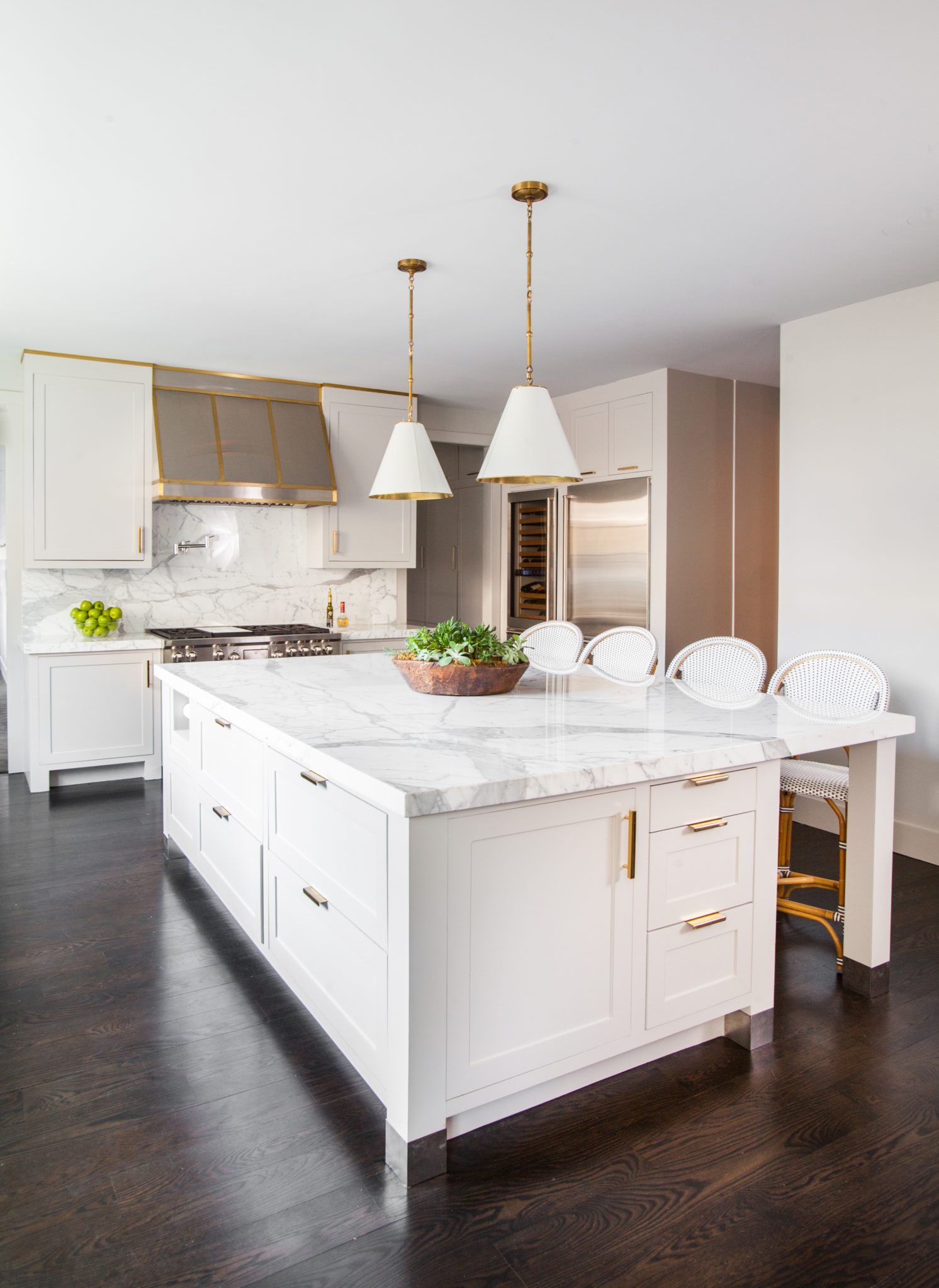 Marble accents and dark wood flooring in a kitchen design by Creative Tonic