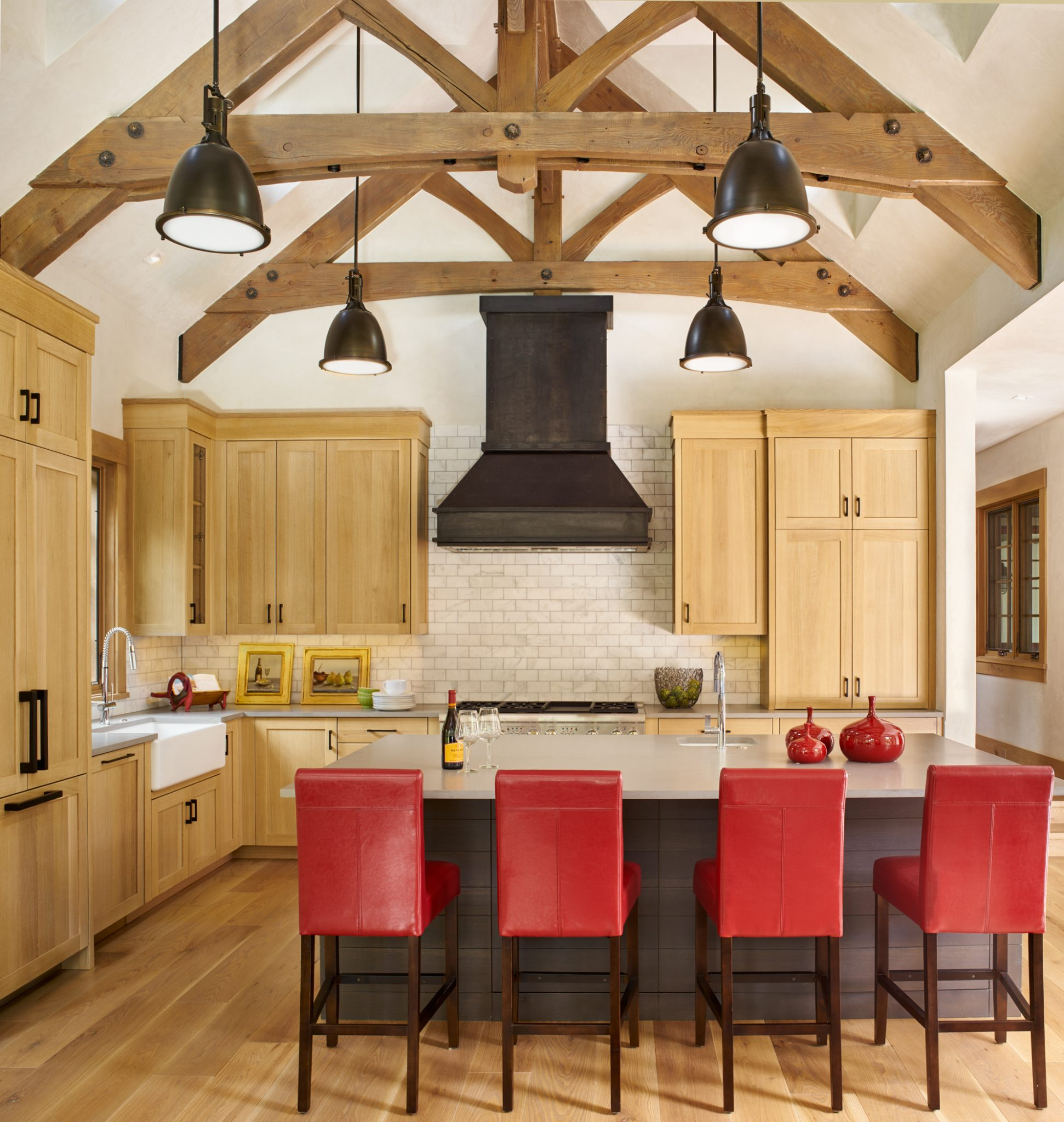 Light wood kitchen with dark stone island and red barstools. by Brewster McLeod Architects