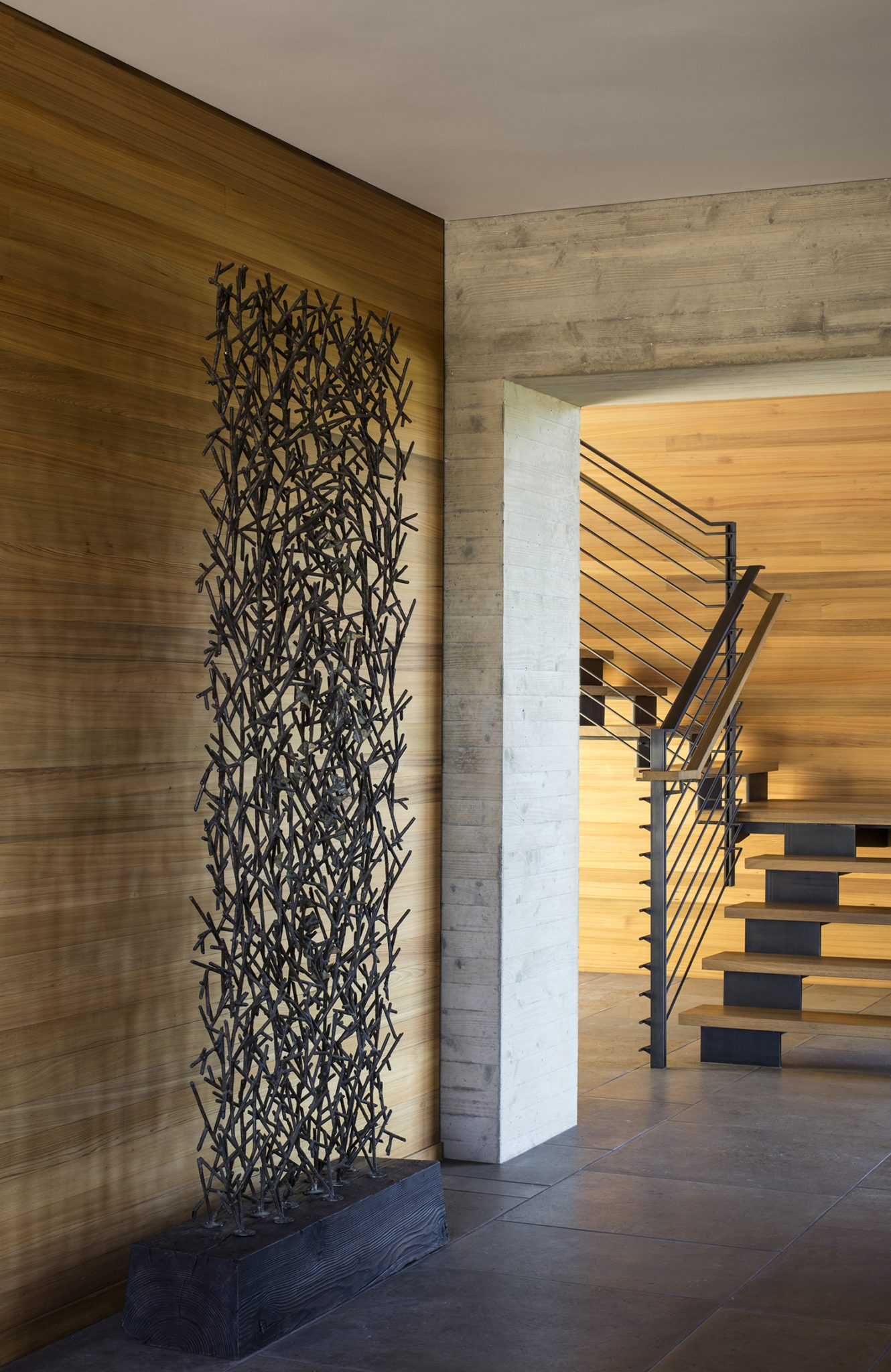 Modern entry hall with sculpture, board-formed concrete, metal and wood stair by Fergus Garber Young Architects