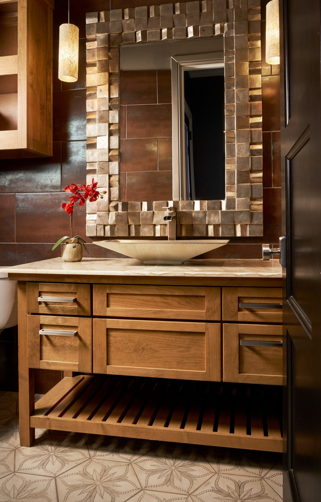 A metallic, elongated vessel sink complements the framed metallic mirror. by Wesley-Wayne Interiors